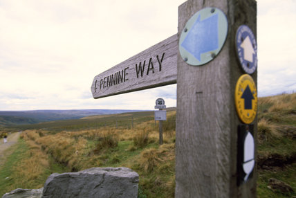 A wooden signpost showing The Pennine Way on this footpath on Buckstones Moor, which is part of the Marsden Moor Estate