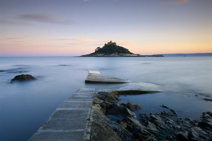 View of St.Michael's Mount silhouetted in a pink dawn, there is a wide view of a calm sea whilst in the foreground the causeway emerges as the tide recedes.