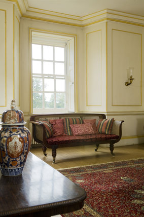 The cane-work sofa from Windsor Castle and eighteenth-century commode by John Cobb in the Entrance Hall at Mottisfont Abbey, Hampshire