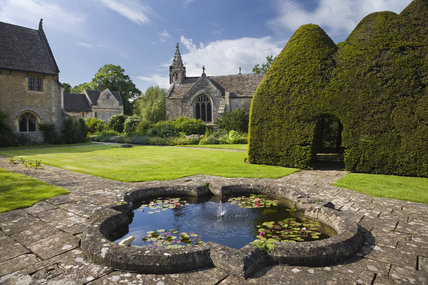 The C14th century Parish Church of All Saints, seen across the lily pond, with part of Great Chalfield Manor visible on the left hand side, Wiltshire