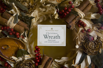 A National Trust natural Christmas wreath with dried fruits, leaves, berries and cinnamon sticks, on sale at the Christmas fair at Lacock Abbey, near Chippenham, Wiltshire