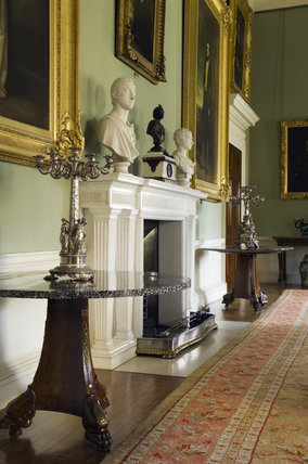 The fireplace and French Empire table with circular granite top and tripod support in the style of Pierre-Antoine Bellange, in the Dining Room at Ickworth, Suffolk