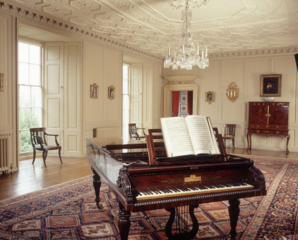 The Drawing Room at Croft Castle was used for musical events, the furnishings include painted early Georgian panelling,a grand piano, chandelier and late Stuart family pastel portraits