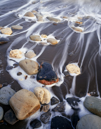 The mosaic effect of seawater and stones on this Durham Coast beach which was once blackened by coal spoilings, now cleansed by the sea since mining waste ceased being dumped