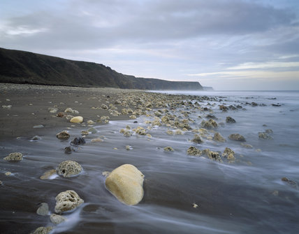Horden Beach on the Durham Coast looking north at dusk along a rocky beach with cliffs in the background forming part of the landscape acquired by the Trust for reclamation after mining