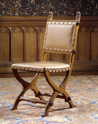 One of a set of four oak X-frame chairs supplied by John G.Crace & Sons, c.1855, at Tyntesfield.