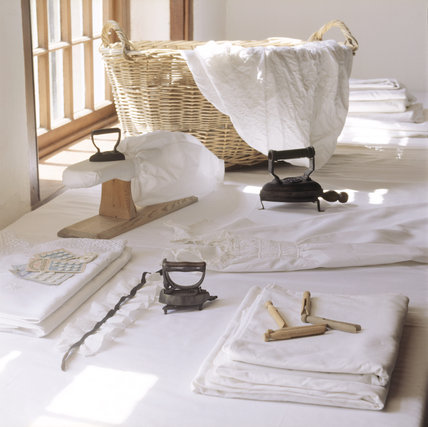 A corner of the Laundry with linen articles and various tools including flat irons, sleeve board, clothes pegs and a clothes basket