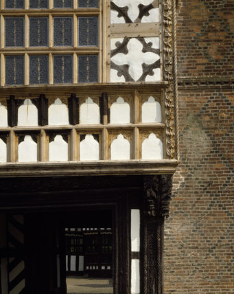 A close up of a corner of Little Moreton Hall revealing how its timbers were arranged in a rich variety of patterns largely within square panels