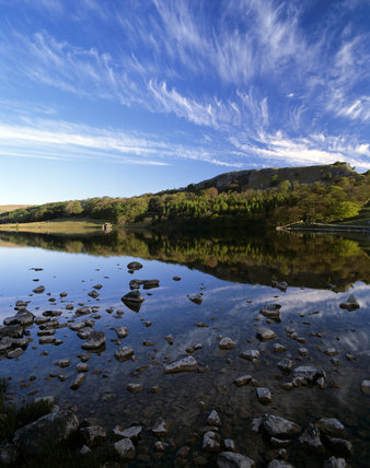 Looking across Malham Tarn, from the rock strewn foreshore, to the distant hills, reflected, perfectly, in the still water