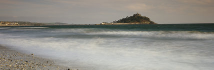 Panoramic view across the sea to St. Michael's Mount in early morning, showing sun shining on the castle and the houses below. Sun also catches white foam breaking over the pebbled beach.
