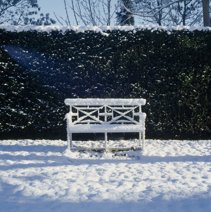 Close view of a snow covered garden seat with a tall hedge behind covered with snow at Osterley Park