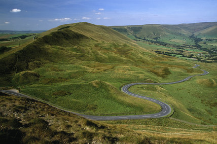 A view of Rushup Edge from Mam Tor in the Peak District with a road winding at the bottom of the hill