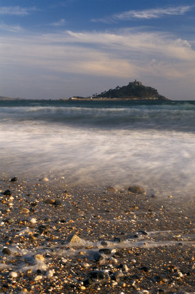 Overall view of St. Michael's Mount from the beach, under a cloudy sky, showing pebbles and sand, waves breaking on the shore and stretch of sea with breakers below the mount.