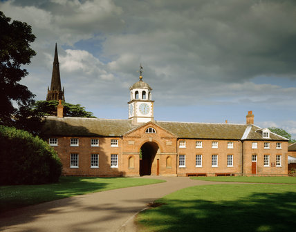 From across the green, the West Front of the Stable Block and Clock Tower above the archway entrance at Clumber Park