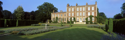 Nearer oblique view of the front of Gunby Hall showing lawns and lavender beds with a sundial