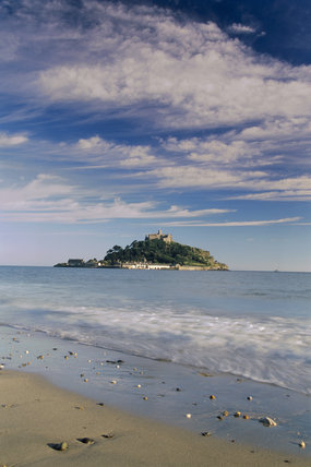 Distant view of St.Michael's Mount with cloudy blue sky and waves breaking on shore, originally site of Benedictine priory. Castle dating from C12th.