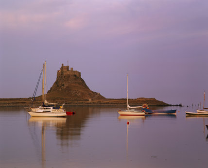 View of small boats and Lindisfarne Castle, Northumberland