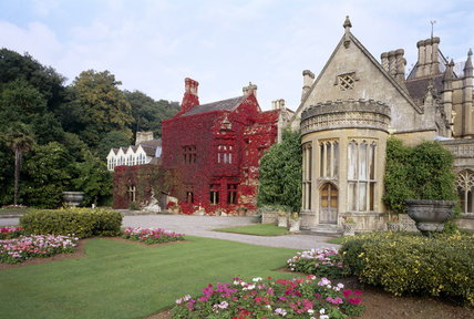 West front of the Victorian Gothic house of Tyntesfield with the bow window of the Drawing Room on the right and the red creeper covered walls of the Billiard Room