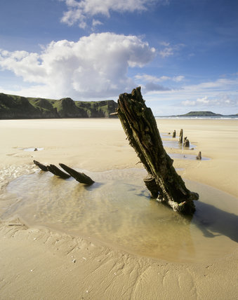 The skeletal remains of a boat sticking out of the sandy beach of Rhossili Bay