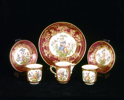 Close view of six pieces from the eighteenth century Chelsea tea service in the French Room at Upton House, decorated with Chinoiserie figures surrounded by gilt trellis work