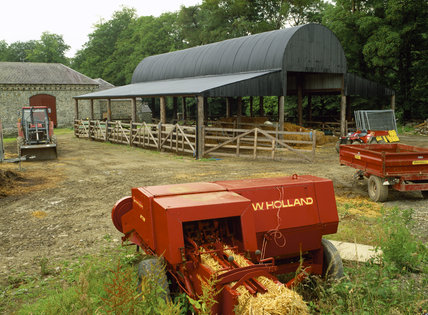 A modern barn with farm machinery and hay stored in the open sided barn at Llanerchaeron