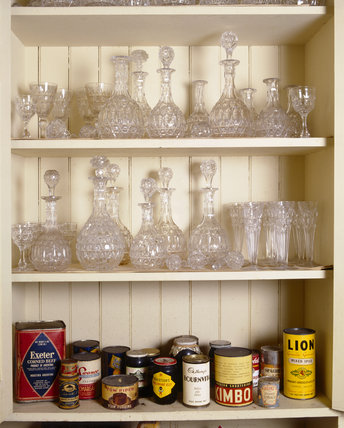 Cut glass decanters on two shelves with tins and groceries on the bottom shelf in a pantry cupboard at Tyntesfield