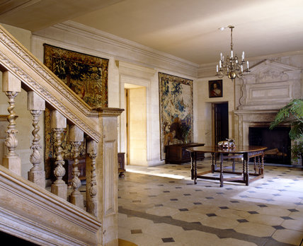 The Hall at Upton House from the bottom of staircase with view to stone chimney-piece in style of William Kent, and the mid C17th Brussels tapestries