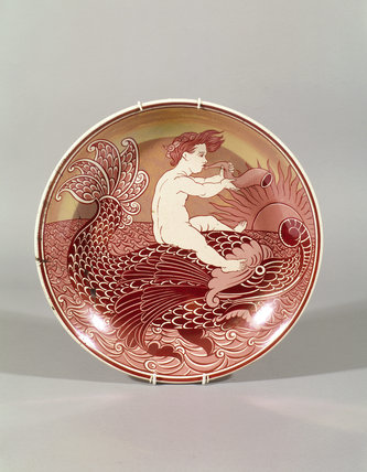One of a set of six red lustre chargers by de Morgan, depicting a boy on a dolphin