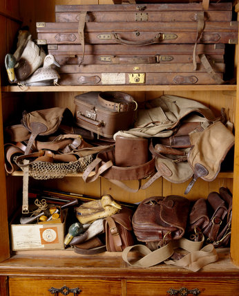 Gun cases, cartridge bags and boxes, a fishing net & decoy ducks on shelves in a cupboard at Tyntesfield