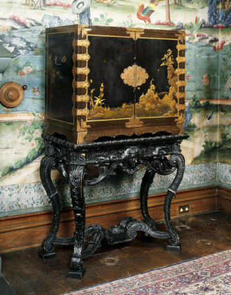 A large late C17th black Japanese lacquer cabinet, decorated with Japanese landscapes at Penrhyn Castle