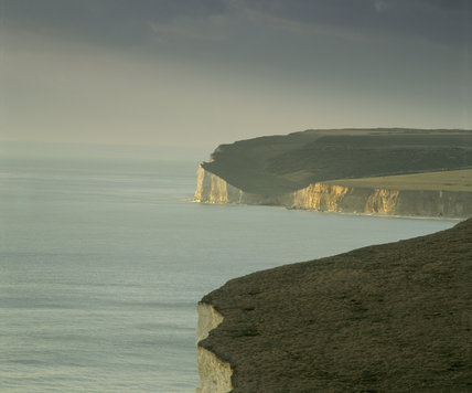 Crowlink, view along the grassland at the top of the cliffs with sunlight on white cliffs in the distance and a calm sea