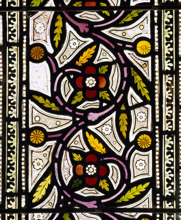 A stained glass window in the Chapel at Tyntesfield depicting a floral scroll in reds and greens