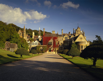 The West Front of Tyntesfield, the Victorian Gothic Revival house designed by John Norton between 1863 and 1866 in tinted Bath Stone showing the driveway and clipped holly trees