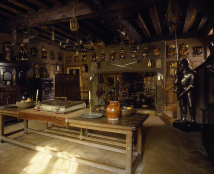 Snowshill Manor - Dragon: general view to North-East corner showing wooden table with candlesticks and jug, fireplace with swords above and a suit of armour