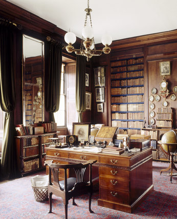 The Library at Erddig with the C18th mahogany library table (in the manner of Thomas Chippendale), desk chair, and corner view of floor to ceiling bookshelves and large mirror on one wall