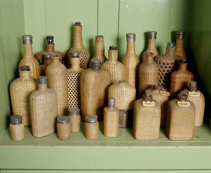 Wicker covered picnic bottles on a shelf in the Butler's sitting room at Tyntesfield