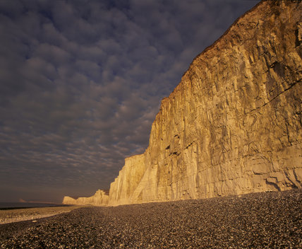 The Seven Sisters stretching along to the Birling Gap, with a shingle beach in the foreground