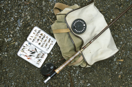 A selection of fishing equipment comprising a rod, reels, a box of flies and haversack laid out on the shingle beach at Loweswater in the Buttermere Valley in the Lake District