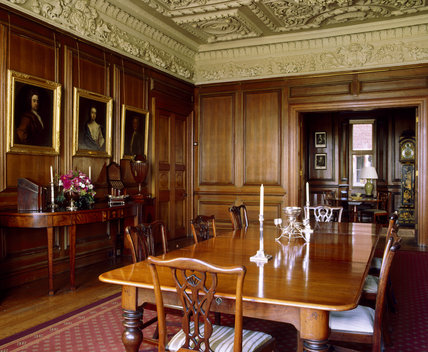 The Dining Room at Dunster Castle looking towards the servery with the servery screen doors open; wood panelled walls a sideboard and a black lacquer longcase clock circa 1730