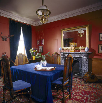 Room view of the Victorian Study looking towards the window showing the square table, chairs, fireplace, mirror, clock on the mantelpiece, china tea service and wooden coal scuttle