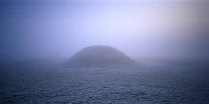View looking towards a large burial mound at Sutton Hoo on a frosty, foggy, dawn morning