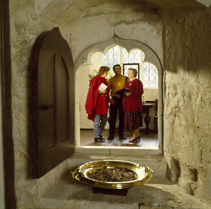 Visitors in the Old Chapel at Ightham Mote, viewed through the squint in the west wall which enabled members of the family to hear services without entering the chapel