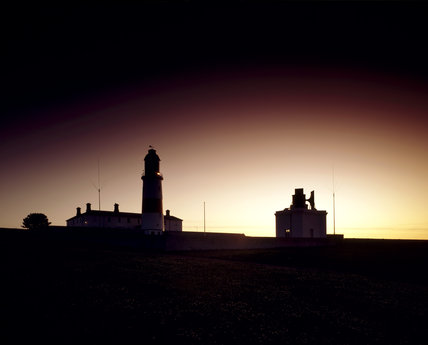 An outline of Souter Lighthouse and fog station against the background of a sunset sky, taken from the coastal path