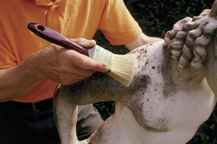 Dry brushing to remove loose dirt from a statue, at Anglesey Abbey