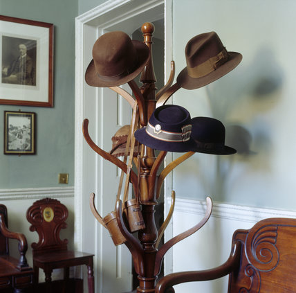 The Back Hall at Berrington Hall showing the hat stand with the 'Anthony Eden' hat used by the present Lord Cawley when at the Bar; his mother's Red Cross and gardening hats