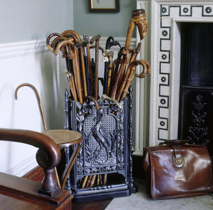 The Back Hall at Berrington Hall showing a selection of walking sticks in a stand, including a 'saw' stick and a prototype of the modern shooting stick; also a leather briefcase