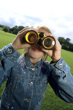 Close shot of a girl looking through binoculars in the grounds of Castle Ward, Co