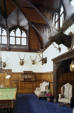 Partial view of Billiard Room at Tyntesfield, showing carved oak panelling, hammer beam roof with raised skylight windows, heated billiard table & trophies of the chase