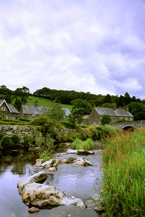 A general view of the river Conwy flowing through Ysbyty Ifan village, Gwynedd, Wales,  showing stone houses and stone arched bridge over the river