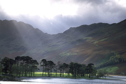 A shot of Buttermere valley from the valley floor looking up towards a mountainous ridge with some trees on the shore of a lake in the foreground, and rays of light permeating the clouds